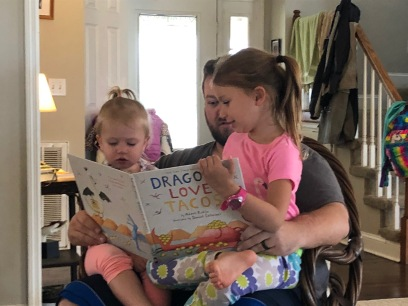 uncle reading with nieces